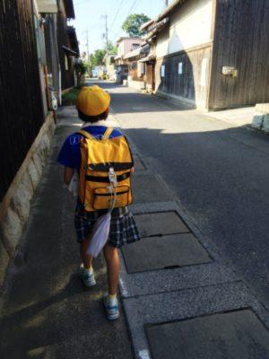 集合場所の神社へ急ぐ次女。首にはタオル、給食当番のエプロンを後ろにひっかけて。